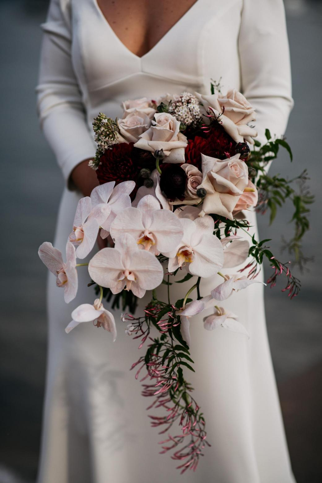 Bride Jordana holds her mixed bridal bouquet, featuring orchids and pink roses; whilst wearing the AUBREY wedding dress by Karen Willis Holmes.