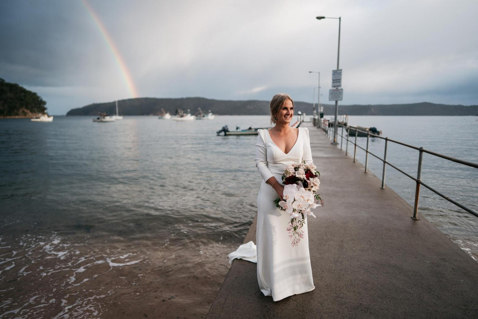 Bride Jordana under rainbow wearing the AUBREY gown by Karen Willis Holmes; featuring a V-neck and long-sleeves.