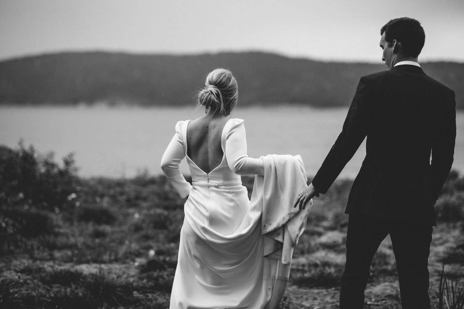 B&W image of KWH bride Jordana and husband Mitch; bride wearing the AUBREY gown with a low back and long train.